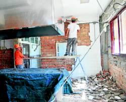 Trabajadores en el interior de la cocina del colegio - Foto:EVA M. HERAS